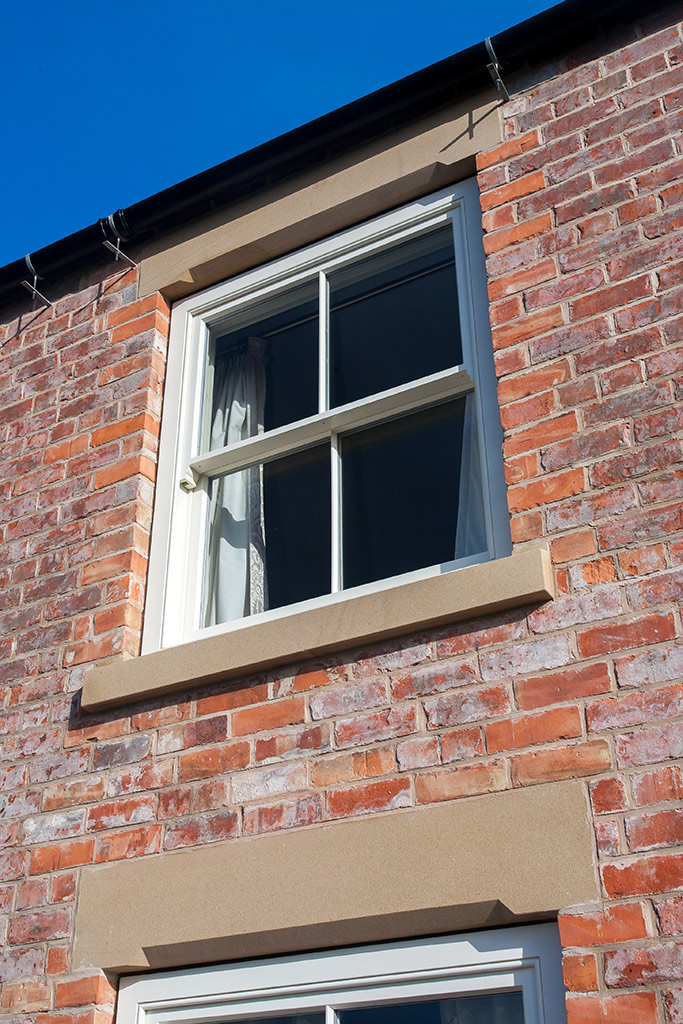 Natural Sand Stone lintol and cill compliment this sliding sash window by Parkwood